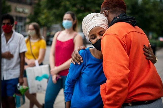 Rep. Ilhan Omar greeted a young voter outside the Dinkytown Target near the University of Minnesota campus in Minneapolis on Tuesday. LEILA NAVIDI – STAR TRIBUNE
