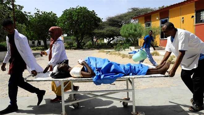 Paramedics carry an unidentified man injured in the explosion in Afgoye in Somalia [Feisal Omar/Reuters]