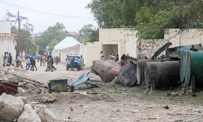 Police survey the scene after a suicide car bomber drove into a checkpoint near the port in Mogadishu. Photograph: Feisal Omar/Reuters