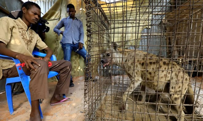 Mohamed Sheikh Yakub, a patient suffering with mental illeness, sits inside the treament room where a hyena believed to exorcise evil spirits that cause mental illness is secured in a cage, in Hodan dirtict of Mogadishu, Somalia - Februray 15, 2020 (Reuters/Feisal Omar)
