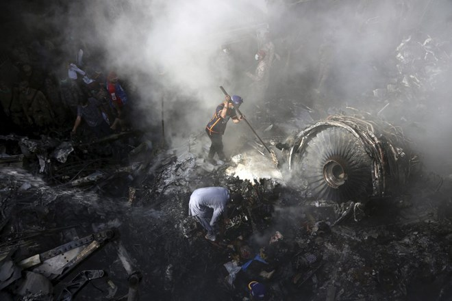 CORRECTS NUMBER OF PASSENGERS TO NEARLY 100, INSTEAD OF MORE THAN 100 - Volunteers look for survivors of a plane that crashed in a residential area of Karachi, Pakistan, May 22, 2020. An aviation official says a passenger plane belonging to state-run Pakistan International Airlines carrying nearly 100 passengers and crew crashed near Karachi's airport. (AP Photo/Fareed Khan)