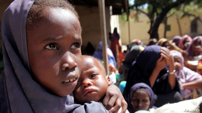An internally displaced Somali girl carries her sibling as they wait to collect food relief from the World Food Program (WFP) at a settlement in the capital, Mogadishu, in 2011.