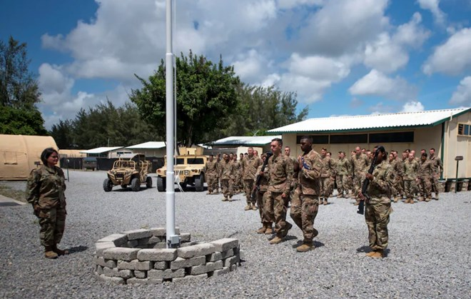 Airmen from the 475th Expeditionary Air Base Squadron conduct a flag-raising ceremony, signifying the change from tactical to enduring operations, at Camp Simba, Manda Bay, Kenya, on Aug. 26, 2019. (Staff Sgt. Lexie West/U.S. Air Force/AP)