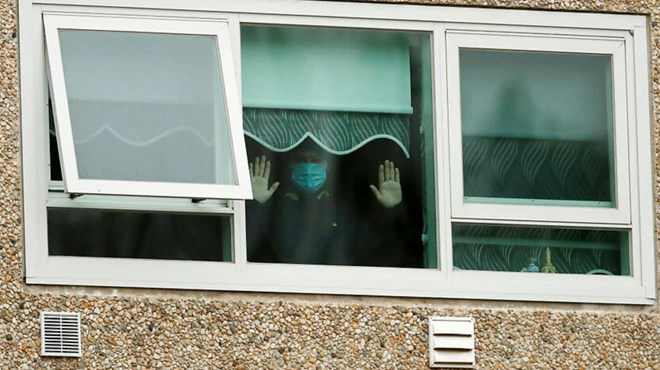 A man is seen looking out a window of the Flemington Towers Government Housing complex. Source: Getty Images
