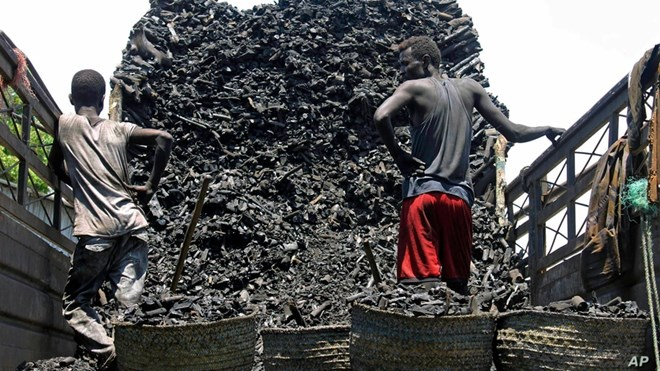 Somali porters offload charcoal from a truck at a charcoal market in Mogadishu, Oct. 30, 2012.