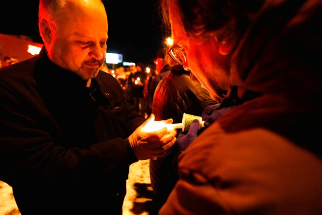 Victor Lieberman (right) lights Dr. Babil Suleiman's candle at Tuesday nights rally in support of the Juba restaurant Jesse Trelstad/ Grand Forks Herald
