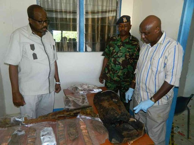 North Eastern regional coordinator Mohamud Saleh and police regional commander Edward Mwamburi inspect the deadly weapons that were found buried outside a commercial residential house in the outskirts of Garissa town. Saleh thanked members of the public for volunteering information on suspected criminals