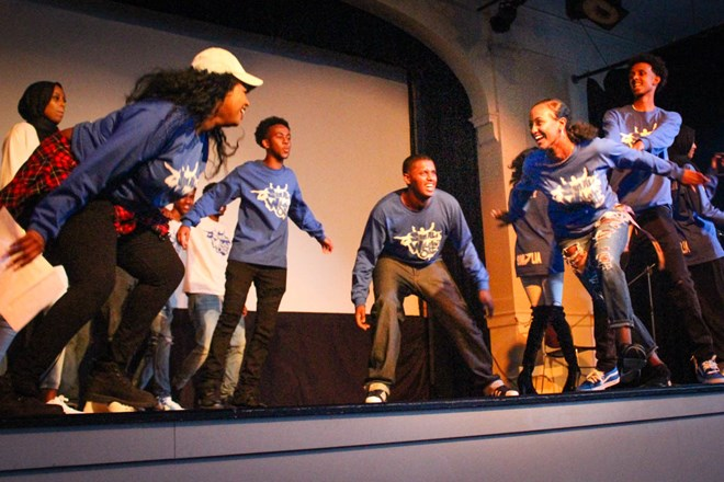 Representing the colors of the Somali flag, a team dressed in blue competes on stage to the amusement of the audience. The youth-organized event raised money for drought relief in Somalia. (Photo by Damme Getachew.)
