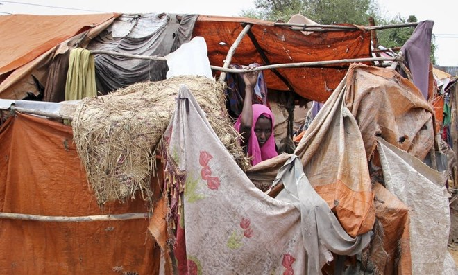 In this photo taken Wednesday, Nov. 16, 2016, Somali refugee and mother of six Madino Dhurow stands by her makeshift shelter in the Daryeel camp for the displaced. Farah Abdi Warsameh | AP 2016