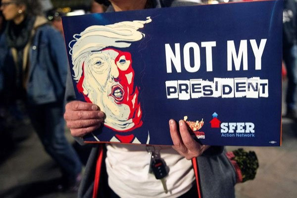 A demonstrator holds an anti-Trump sign during a President's Day protest march in Denver, Colorado on February 20, 2017. PHOTO | JASON CONNOLLY | AFP