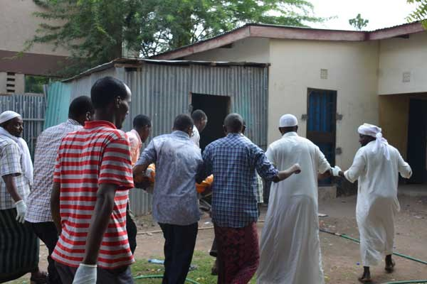 Residents assist police officers to carry away the body of one of the three people found murdered in Garissa Town on February 23, 2017. PHOTO | ABDIMALIK HAJIR | NATION MEDIA GROUP