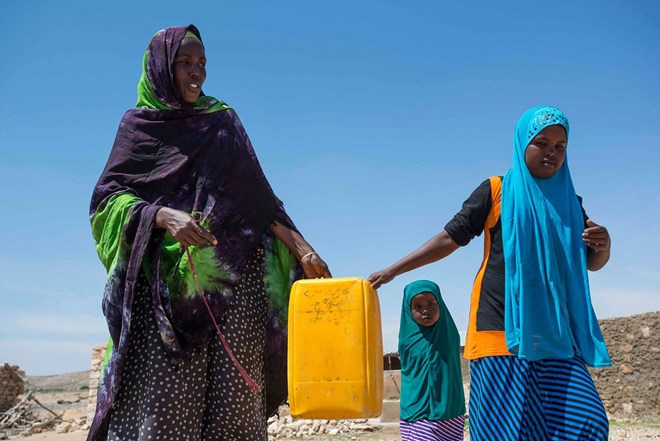 A resident of Rabaable village in Somalia fetches water with the help of her daughters. The villages well was recently rehabilitated by UNICEF. Photo: UNICEF Somalia/Sebastian Rich