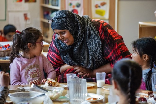 Sabah Saed works with Kent Family Center preschool children during their lunch in Kent. Saed started as a parent volunteer working in the preschool program and now is an assistant teacher. (Steve Ringman/The Seattle Times)