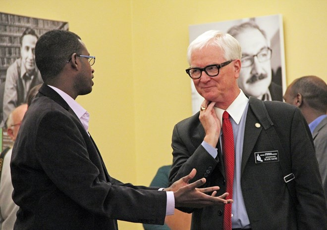 Sandol Khalaf of Shanta Link, a Somali-run scholarship program based in St. Paul, strikes up a conversation with Rep. Duane Sauke, DFL-Rochester, at a Capitol sambusa event on Jan. 23, 2017. Laura Yuen | MPR News