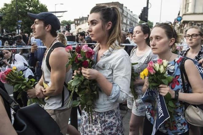People carrying bunches of colourful roses gather for a vigil after an attack on a mosque near Finsbury Park (JEREMY SELWYN)