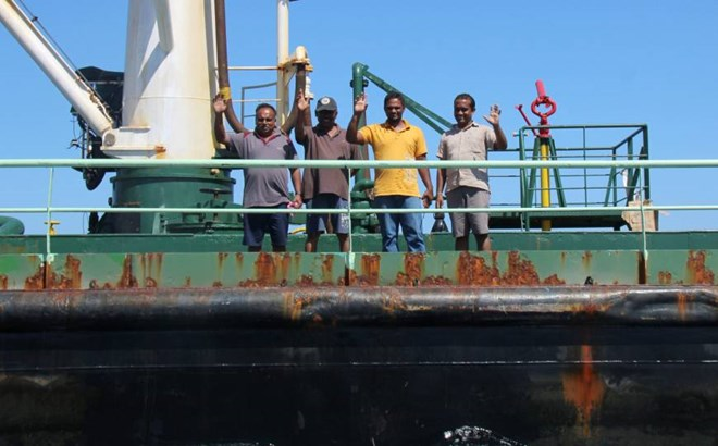 Crew members are seen aboard the oil tanker Aris-13, which was released by pirates, as it sails to dock on the shores of the Gulf of Aden in the city of Bosasso, northern Somalia's semi-autonomous region of Puntland, Sunday. | REUTERS