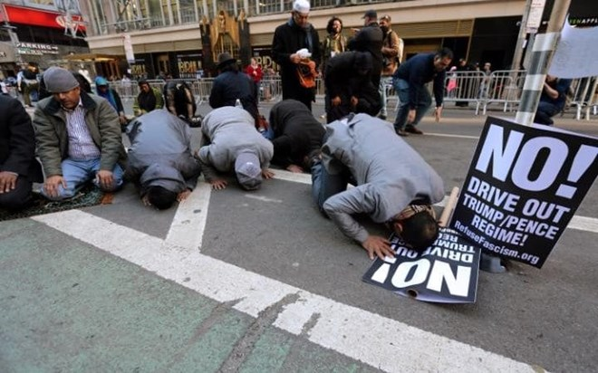 Muslim men kneel on Broadway Ave. as they take part in afternoon prayers CREDIT: CARLO ALLEGRI/X90181