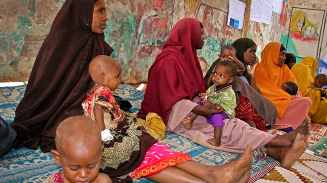 FILE - In this photo taken March 25, 2017, Somali women and their malnourished children attend a health center in Baidoa, Somalia.