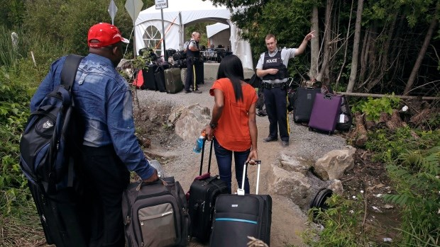 An RCMP officer speaks to people as they cross the border into Canada at Roxham Road in Hemmingford, Que., earlier this year. The RCMP created an interview guide for officers handling the asylum seekers. (Charles Krupa/Associated Press)