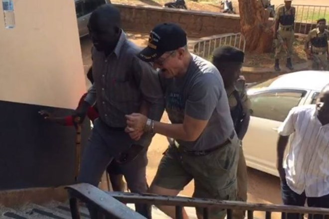 Mr Jimmy Taylor (right) after Ugandan police arrested him on August 18, 2018 after viral video showed him assaulting hotel workers in Kampala. PHOTO | TWITTER