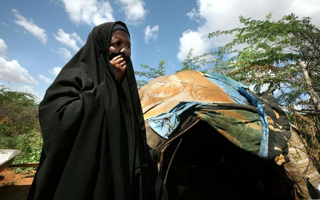 A refugee woman from Imey, a town in the Gode zone of Ethiopia's Somali Region, stands outside her makeshift home in Dadaab refugee camp in northern Kenya. She and her children fled to Kenya after her husband was killed by Ethiopian forces in December 2007. © Evelyn Hockstein