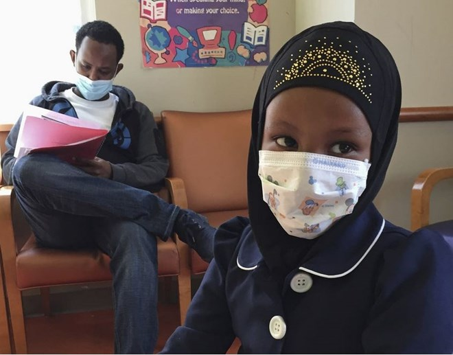 In this 2017 photo, Amira Hassan, of Burnsville, Minn., plays in the waiting room at the specialty clinic at Children's Minnesota in Minneapolis, while her dad, Mohamud Hassan, fills out paperwork. A year after a measles outbreak, the vaccination rates in Minnesota have increased 16 percentage points among Somali-American children. Amy Forliti | AP