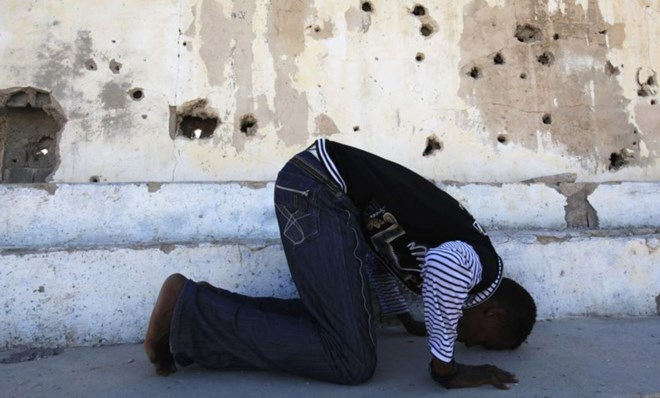 FILE - Somali athlete Abdullah Bare Kuulow prays after a training session in preparation for the 2012 London Olympic Games inside Mogadishu Stadium, March 16, 2012. AFRICOM troops have relocated from the complex, returning its main focus to athletics.