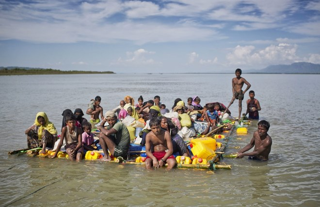 "FILE- In this Nov. 11, 2017 file photo, Rohingya Muslims travel on a raft made with plastic containers on which they crossed over the Naf river from Myanmar into Bangladesh, near Shah Porir Dwip, Bangladesh. Six months after waves of attacks emptied Rohingya villages in Myanmar, sending 700,000 people fleeing into Bangladesh, there are few signs anyone is going home soon. Life isn't easy in the refugee camps, but the Rohingya living there have one immense consolation. ""Nobody is coming to kill us, that's for sure,"" says one man. (AP Photo/A.M. Ahad, File)"