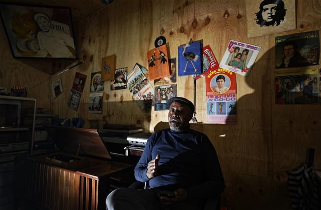 "In this photo taken Thursday, March 1, 2018, James ""Jimmy"" Rugami recounts his story inside his vinyl records stall in Kenyatta Market in Nairobi, Kenya.   (AP Photo/Ben Curtis)"