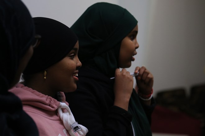 Suweyda (middle) and Salma (right) watch as others continue to dance. Esther taught her children to cook Somali food, showed them Somali culture on TV and danced with them at home as well. Esther said she knows it's different because her children have never been to Somalia. (Photo by Ester Ouli Kim.)