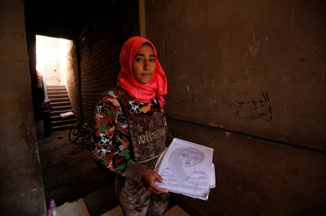 Amany Shamekh, 16, holds her drawing and poses for a photograph at her home in Awlad Serag village of Assiut Governorate, south of Cairo, Egypt, February 8, 2018. Picture taken February 8, 2018. REUTERS/Hayam Adel