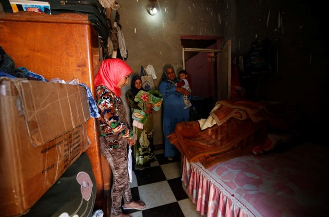 Amany Shamekh (L), 16, stands near her mother Zeinab (R) with Reem Mamdouh (C), 26, wife of Amany's brother at their home in Awlad Serag village of Assiut Governorate, south of Cairo, Egypt, February 8, 2018. Picture taken February 8, 2018. REUTERS/Hayam Adel