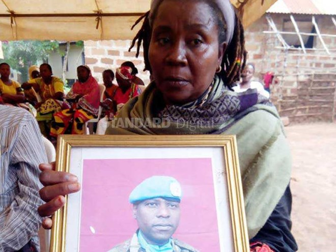 Marieta Kenga holds a potrait of his fifty one year old brother Henry Matano Kenga at the Kambi village in Kaloleni. [Gideon Maundu/Standard]