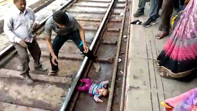 Miracle baby emerges unscathed after falling onto tracks and under moving train