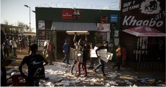 FILE - Looters take items from a foreign-owned shop in Soweto, Johannesburg, Aug. 29, 2018, during unrest that erupted after a foreign shop owner allegedly shot and killed a member of the community during a demonstration.